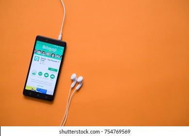 London, november 14, 2017: Bitmoji application in google play store on orange background