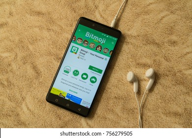 London, november 14, 2017: Bitmoji application in google play store on sandy background and earphones