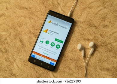 London, november 14, 2017: Google analytics application in google play store on sandy background and earphones