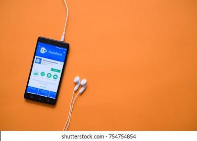 London, november 14, 2017: Microsoft sharepoint application in google play store on orange background
