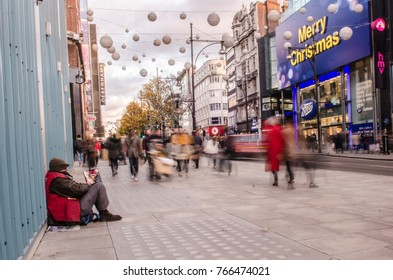 LONDON- NOVEMBER, 2017: A homeless man sits on the busy Oxford Street shopping area in London opposite a Merry Christmas sign highlighting the tragic juxtaposition between the people of London.
