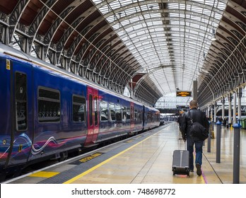 LONDON- NOVEMBER, 2017: A man with a suitcase walking on a platform to his train in London's Paddington Station.