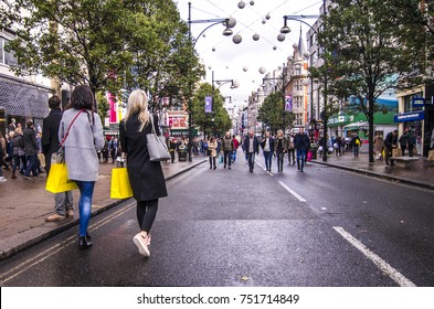 LONDON- NOVEMBER, 2017: Two female shoppers with shopping bags walk down London's most famous shopping location, Oxford Street below the 2017 Christmas lights