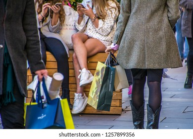 LONDON- NOVEMBER, 2018: A crowded shopping street scene with people carrying shopping bags and young people on mobile phones