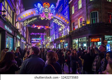 LONDON - NOVEMBER 23, 2018: Black Friday holiday shoppers crowd the fashion district of Carnaby Street, decorated with Bohemian Rhapsody themed Christmas lights strung above brightly lit shop windows.