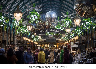 LONDON - NOVEMBER 26, 2018: Holiday shoppers browse the stands of Apple Market, an indoor colonnade in Covent Garden that once housed fruit and vegetable vendors, now filled with crafts and antiques.