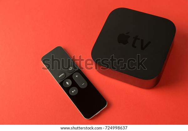 LONDON - NOVEMBER 30, 2015: Apple TV device with remote control on bright red background