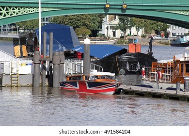 London, October 2016 - A small boat with a hull decorated in the Union Jack Flag is moored alongside the River Thames
