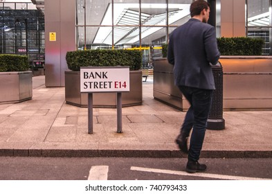 LONDON- OCTOBER, 2017: A business man walks past Bank Street E14 sign in Canary Wharf financial district, London.