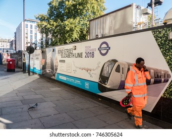 London, October 2017. A construction worker walking past construction hoarding at the new, Bond street, Elizabeth line station, located in Hanover Square.