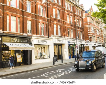 LONDON- OCTOBER, 2017: Fashion shops and a coffee shop on Marylebone High Street with a London black cab driving past.