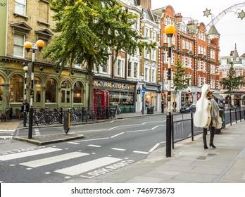 LONDON- OCTOBER, 2017: A zebra crossing on Marylebone High Street, London with pubs, restaurants and fashion shops