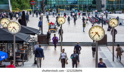 LONDON- OCTOBER, 2018: Business people walking in Canary Wharf by the iconic clock installation, London's financial district