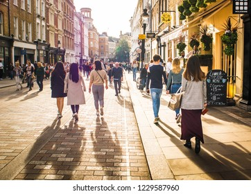 LONDON- OCTOBER, 2018: Shoppers walking past high street shops Covent Garden area of London's west end