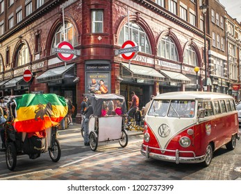 LONDON- OCTOBER, 2018: London street scene outside Covent Garden underground station with a VW Campervan and tricycles outside