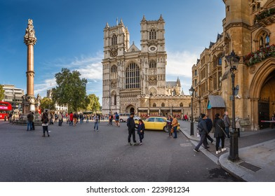 LONDON - OCTOBER 5, 2014: Westminster Abbey is a large gothic church and the traditional place of coronation for English monarchs and tourists walking in front of the gate.