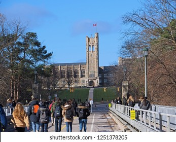 LONDON, ONTARIO, CANADA - DECEMBER 2018:  Students cross a bridge on their way to the campus of  the University of Western Ontario, with the gothic tower of University College in the background.