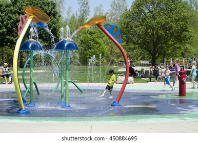 London Ontario, Canada - May 23, 2016:  Unidentified people in the city park and children playing in the aqua amusement park  area during summer  as editorial