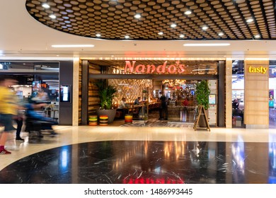 LONDON PADDINGTON, UNITED KINGDOM - JULY 20, 2019: Nando's entrance. Nando's is an international casual dining restaurant chain originating from South Africa, with a Mozambican/Portuguese theme