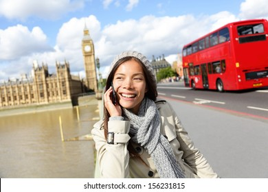 London - professional business woman on smartphone smiling happy. Young happy casual woman talking on smart phone walking outdoor in fall or winter on Westminster Bridge, London, England. Asian model.