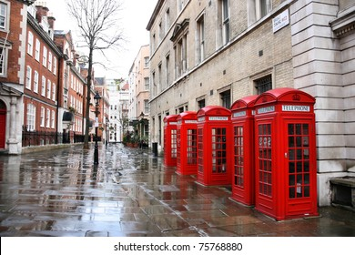 London in the rain - row of red telephone boxes at Broad Court. Covent Garden district.