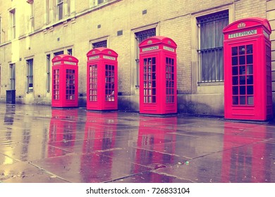 London - red telephone boxes in wet rainy weather. Retro filtered colors style.