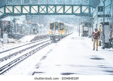 London Road Railway Station, Brighton, UK. 27th February 2018, Train pulls in to London Road station while it snows heavily.The harsh winter weather puts the english railway service to test