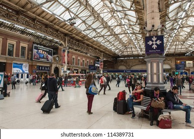 LONDON - SEP 30: Passengers wait for train arrivals at Victoria Station on a crowded Sunday afternoon. September 30, 2012.