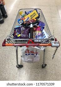 LONDON - SEPTEMBER 1, 2018: Full shopping trolley in the aisles of Sainsbury's supermarket in London, UK.