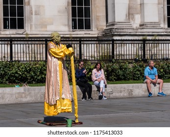 LONDON - SEPTEMBER 2, 2018: A street artist, dressed as Yoda,  floats at Trafalgar Square in central London.