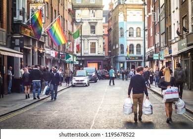 LONDON- SEPTEMBER, 2018: Shoppers walking down a Soho street in London's westend past a bar with a LGBT rainbow flag