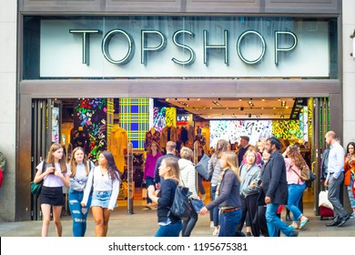 LONDON- SEPTEMBER, 2018: Young colourful shoppers outside the Topshop store on Oxford Street, a world famous retail location and London landmark