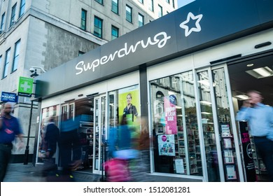LONDON- SEPTEMBER, 2019: Superdrug Store branch exterior signage and logo with motion blurred people.  A health and beauty retailer
