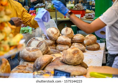 LONDON - SEPTEMBER 27, 2019: Shopkeeper interacting with customers at a bread stall in Borough Market, London. The shopkeeper has passed a plastic bag to the customer.