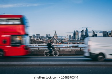 London skyline background with moving traffic of bus, van and bicycle in the foreground