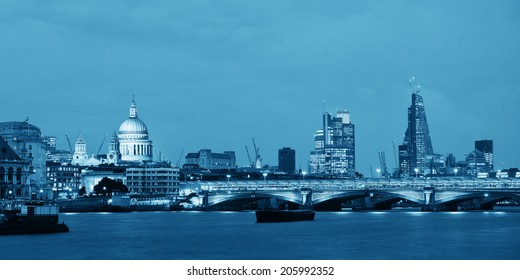 London skyline at night with bridge and St Pauls Cathedral over Thames River.