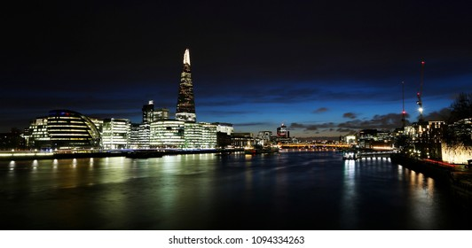 London Skyline at night, include City Hall, skyscrapers, London Bridge, seeing from Tower Bridge at low tide.