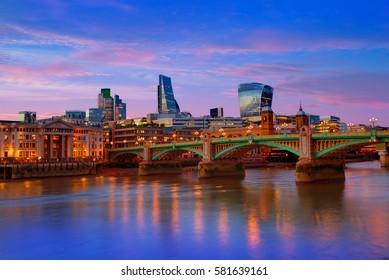 London skyline sunset in Southwark bridge at Thames river UK