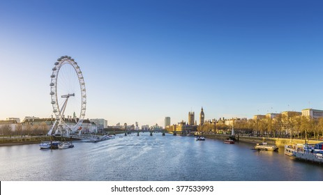 London skyline view at sunrise with famous landmarks, Big Ben, Houses of Parliament and ships on River Thames with clear blue sky - England, UK