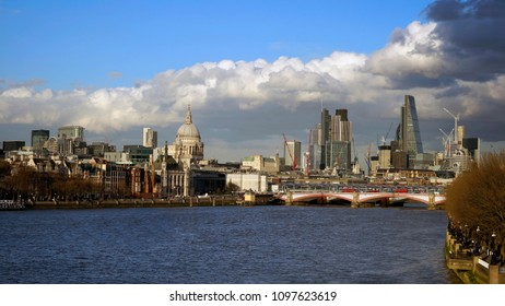 London skyline from Waterloo Bridge. Blackfriars Bridge, River Thames, and skyscrapers present, clouds over blue sky shows dramatic atmosphere