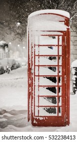 London Snow: A snow covered traditional red British telephone box in Pimlico, London, UK