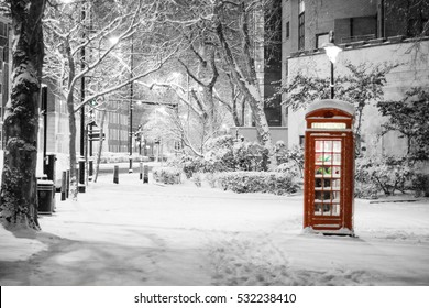 London Snow: Pretty snow scene of traditional red telephone box, The Embankment, City of Westminster, London, UK