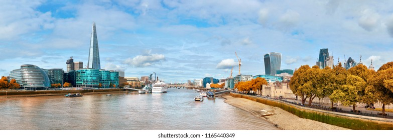 London, South Bank Of The Thames on a bright day in Autumn. Panoramic image taken from the Tower bridge.