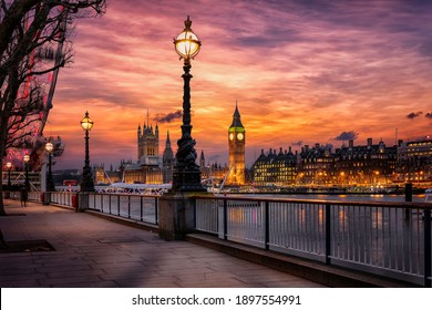 The London southbank riverside of the Thames with view to the Big Ben clocktower and Westminster Palace during a colorful sunset, United Kingdom