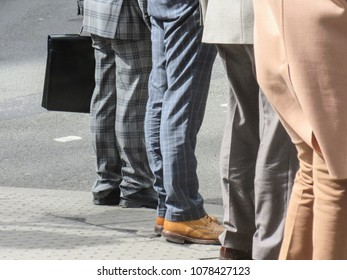London street photograph- lower half of well dress business men with different suits and briefcase on a street in west London