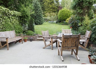 London suburban garden with wooden garden furniture on a patio