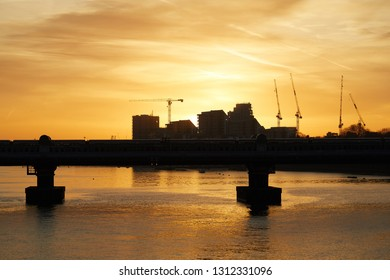 London sunrise. The sun rises over new building developments looking towards Wandsworth (from Putney Bridge), with a train passing over Fulham Railway Bridge in foreground.