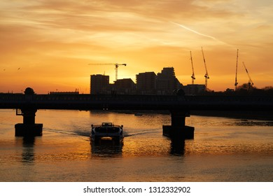 London sunrise. The sun rises over new building developments looking towards Wandsworth (from Putney Bridge), with a catamaran passenger boat passing under Fulham Railway Bridge in the foreground.