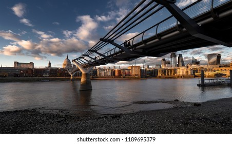 London at sunset, Millennium bridge leading towards illuminated St. Paul cathedral over Thames river