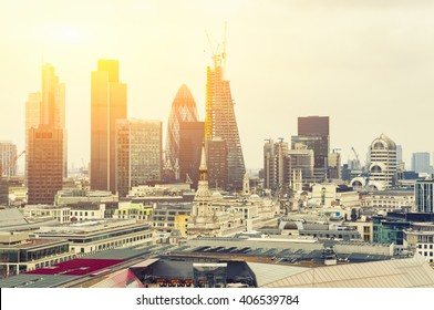 London At Sunset, yellow sun light over London City Center - View on business modern district and Canary Wharf at the background.